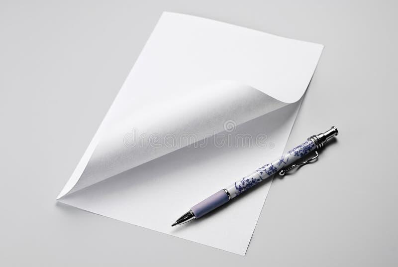 Page de papier blanche avec le coin et le stylo courbés photos stock
