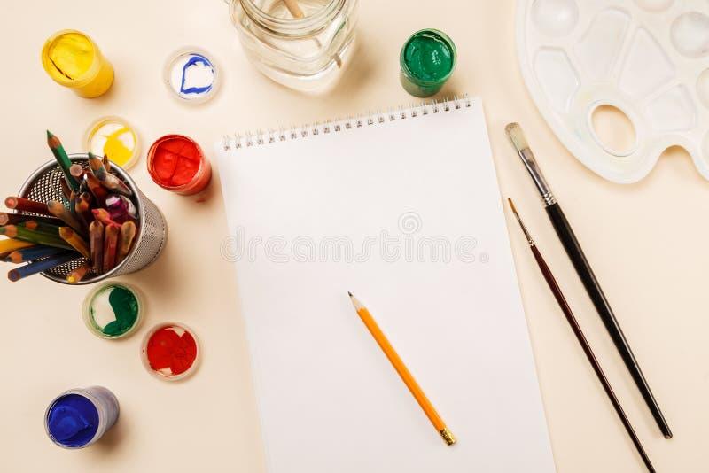 Page de papier blanche, crayons, pots de peinture sur une table, vue supérieure photographie stock