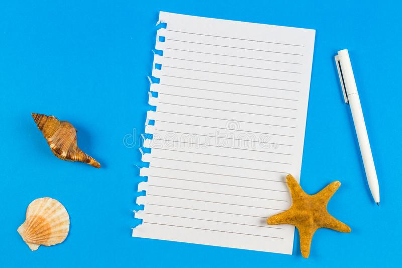 Page ripped off from the notebook, seashells and starfish on blue background. Vacation, travel concept royalty free stock photo