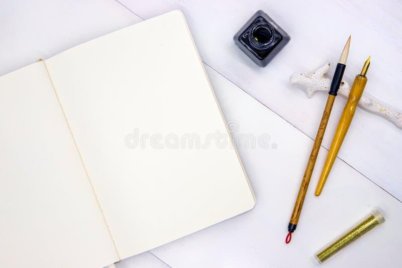 Page vide de carnet à dessins Photo de vue supérieure de carnet sur le fond blanc L'appartement minimal s'étendent avec des outil photographie stock libre de droits