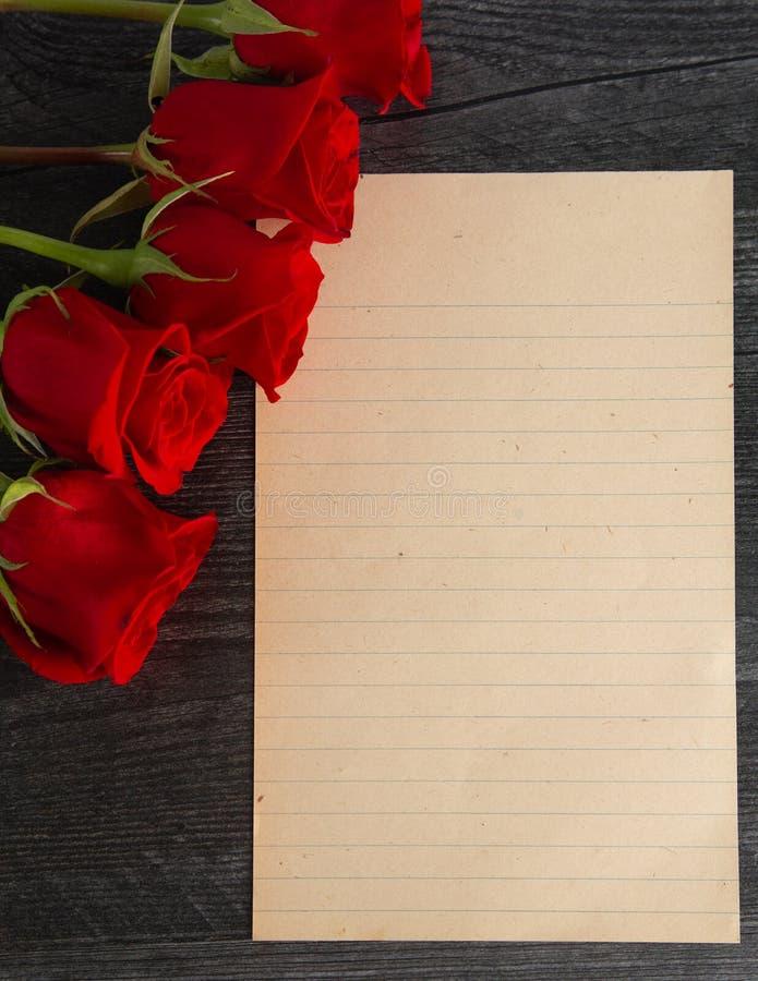 Page vide pour une lettre d'amour avec les roses rouges photographie stock libre de droits