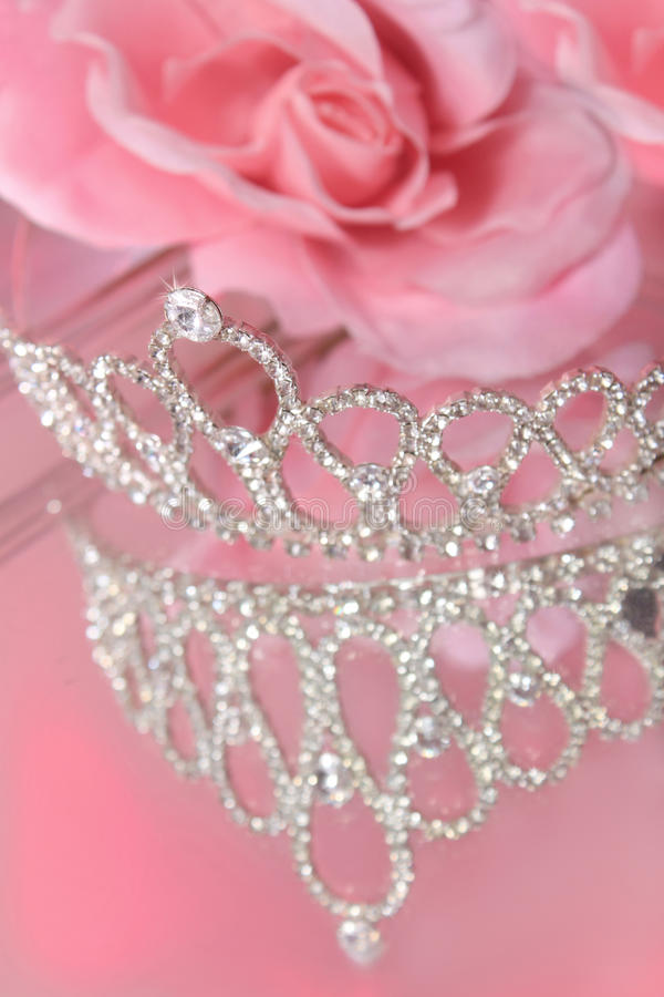 Pageant crown. Mirror reflection of a beautiful diamond or rhinestone crown for a beauty pageant or wedding, with pink roses in the background royalty free stock photo