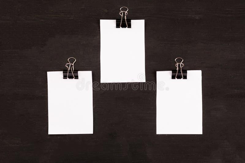 Pages blanches du livre blanc avec le trombone sur un fond noir photos libres de droits