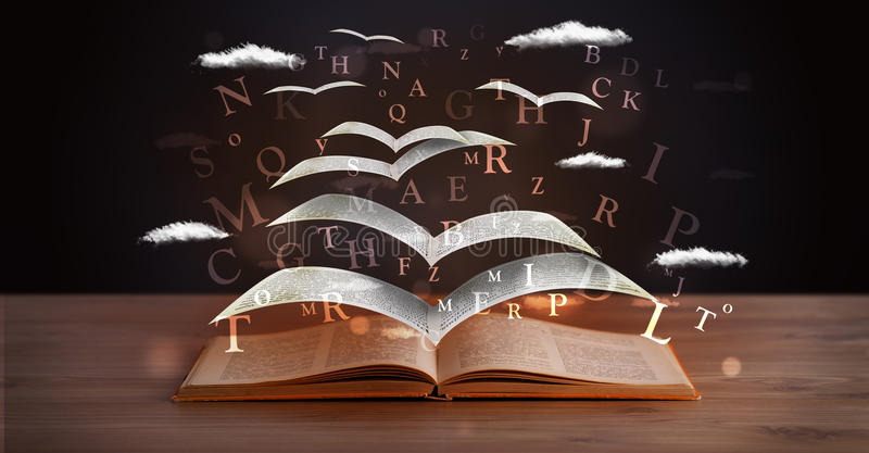 Pages and glowing letters flying out of a book. On wooden deck royalty free stock photo