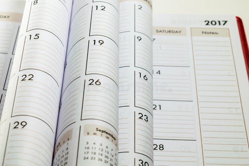 Pages pliées de calendrier au foyer avec brouillé 2017 à l'arrière-plan photos stock