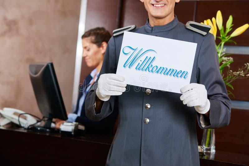 Pagina alla ricezione dell'hotel che tiene il segno di Willkommen fotografie stock