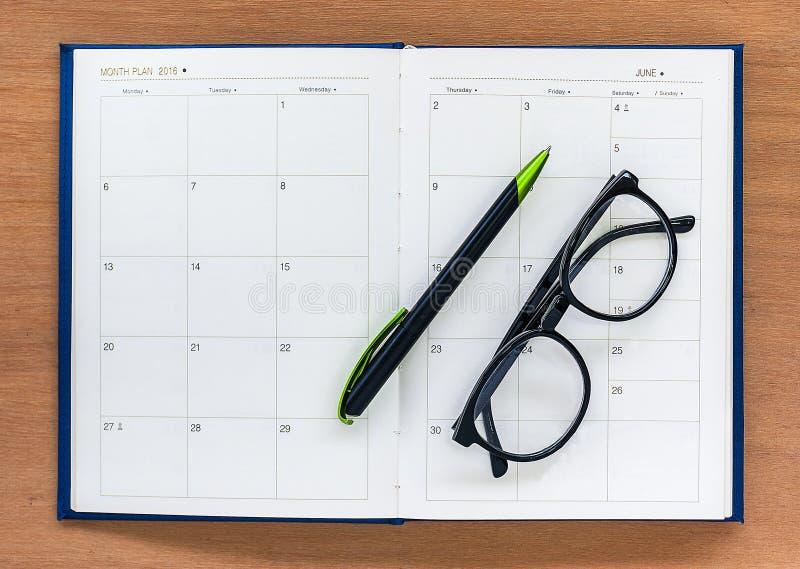 Pagina aperta del calendario del libro del pianificatore del diario con i vetri e penna su Th fotografia stock libera da diritti