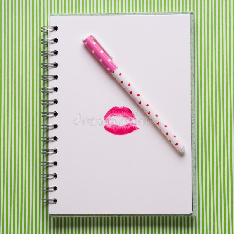 Pagina bianca con la penna di ragazza ed il bacio fotografia stock libera da diritti
