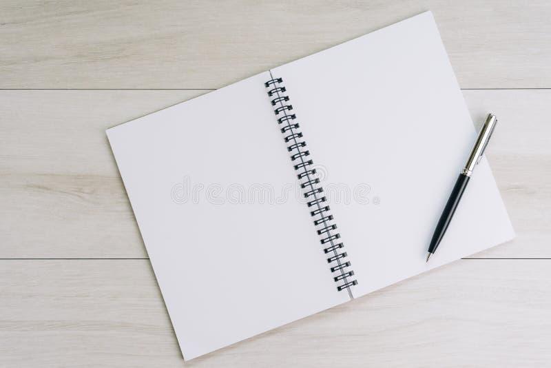 Pagina in bianco bianca del taccuino e della penna dal lato destro con fotografie stock