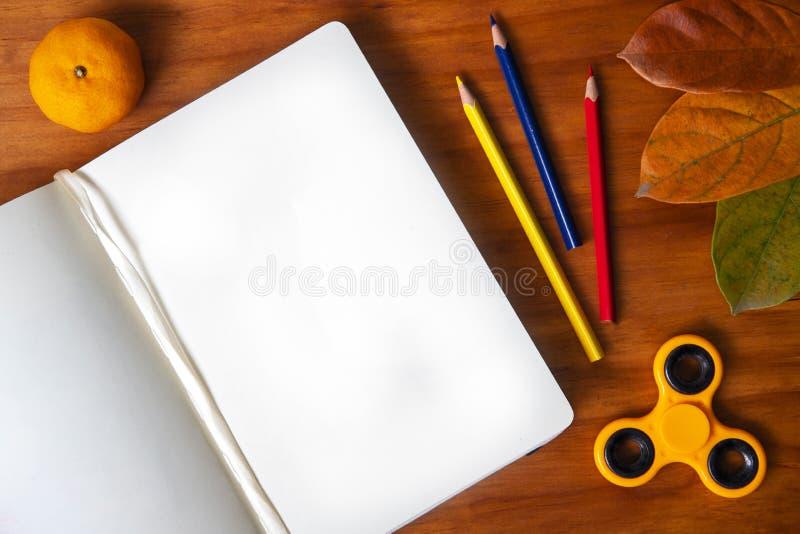 Pagina in bianco dei puntelli di autunno e dello sketchbook su fondo di legno Vista superiore del libro aperto di schizzo immagine stock libera da diritti