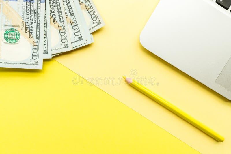 Pagina in bianco del modello con il computer portatile ed il denaro contante su fondo giallo Vista superiore con lo spazio della  immagini stock