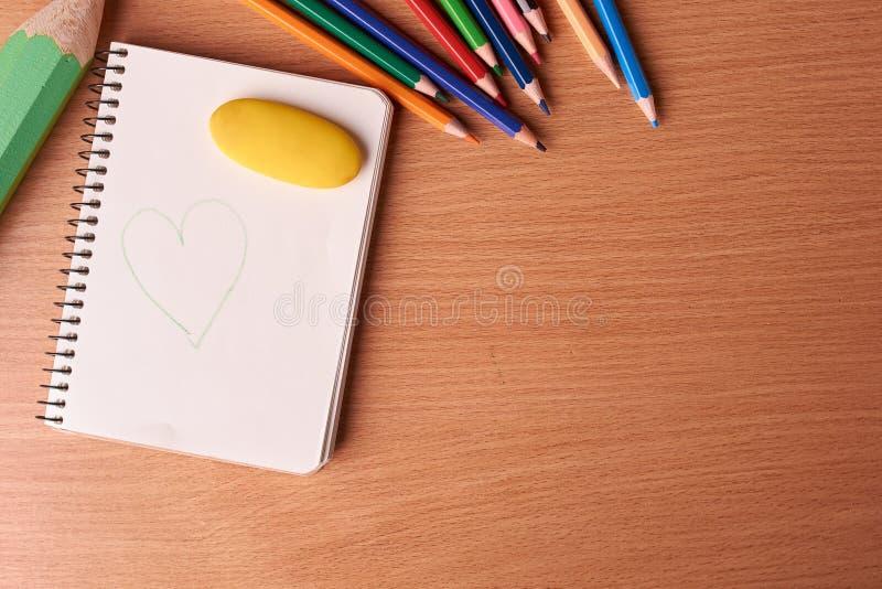 pagina in bianco del taccuino con le matite colorate sulla tavola fotografia stock