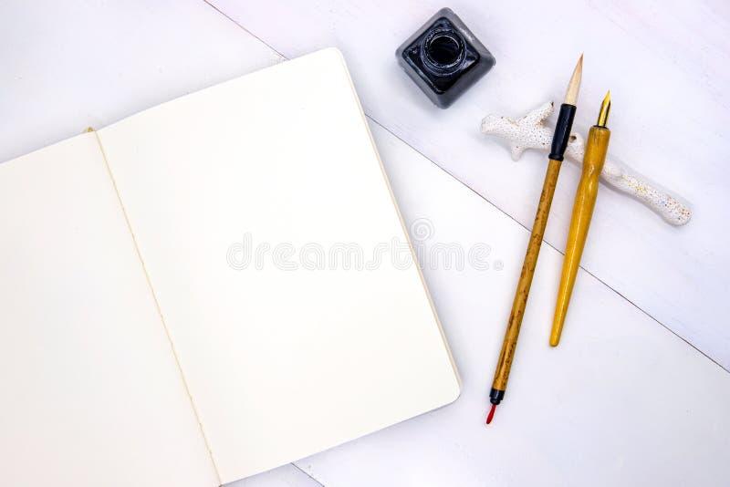 Pagina in bianco dello sketchbook con la spazzola calligrafica, il punto ed il barattolo nero dell'inchiostro Disposizione minima fotografie stock