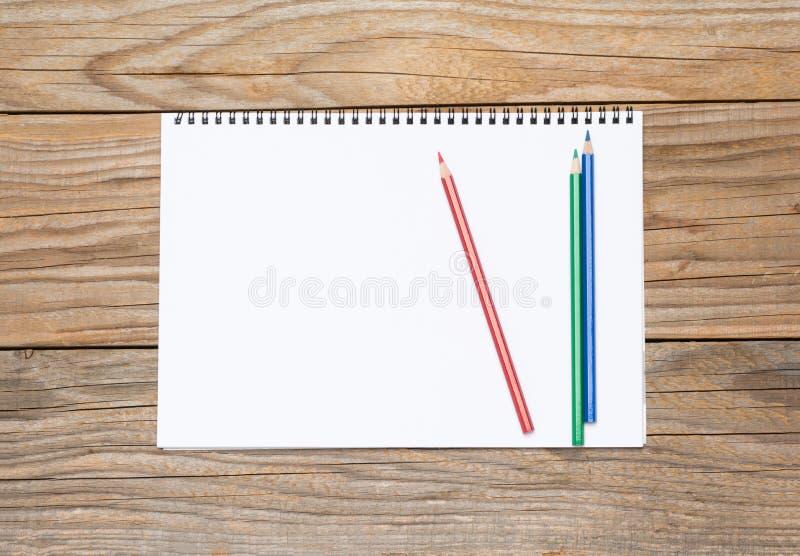 Pagina in bianco di uno sketchbook con le matite colorate immagine stock libera da diritti