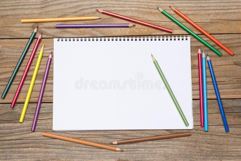 Pagina in bianco di uno sketchbook con le matite colorate fotografie stock libere da diritti
