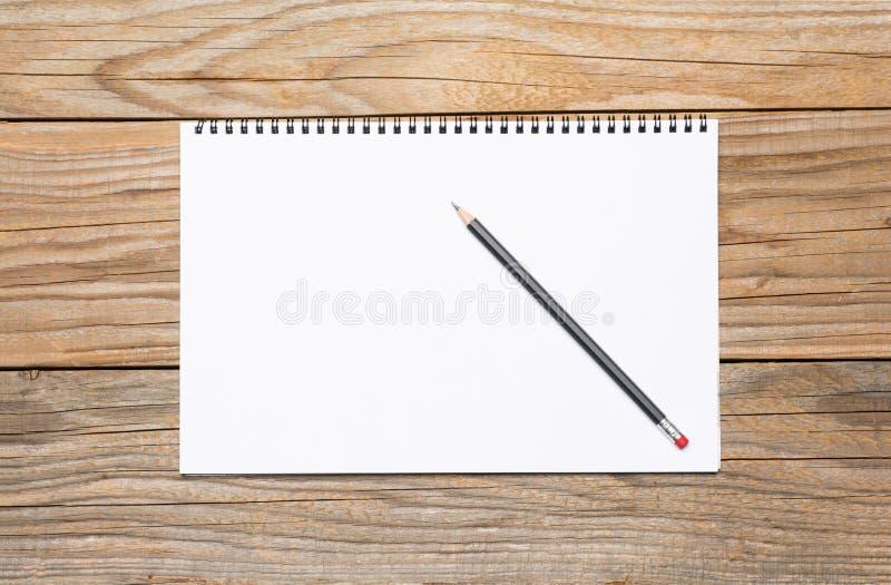 Pagina in bianco di uno sketchbook con una matita nera fotografia stock libera da diritti