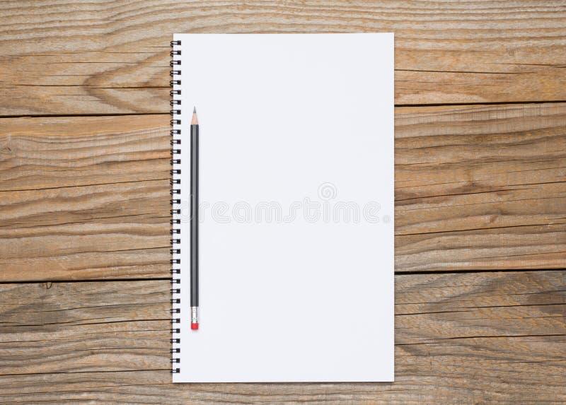 Pagina in bianco di uno sketchbook con una matita nera fotografia stock
