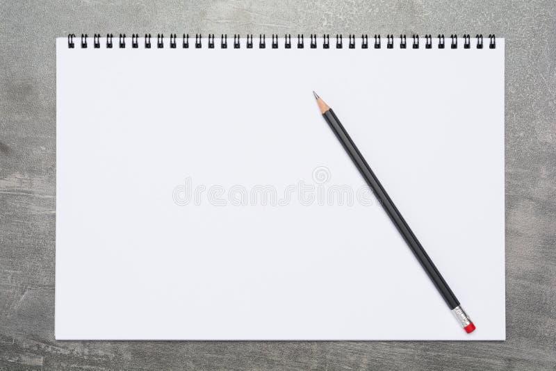 Pagina in bianco di uno sketchbook con una matita nera su una superficie grigia fotografia stock libera da diritti