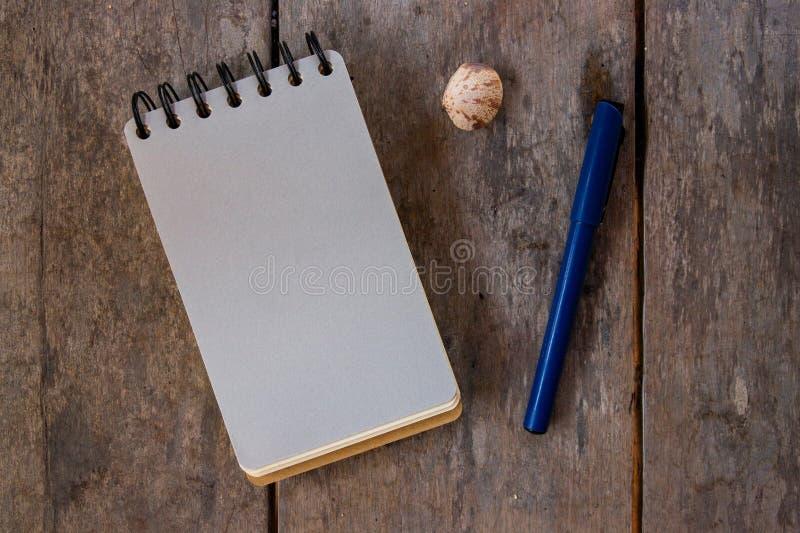 Pagina in bianco e penna del blocco note a spirale su fondo di legno Foto vuota di vista superiore dello sketchbook Blocco note d fotografia stock libera da diritti