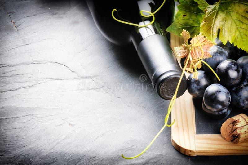 Pagina con la bottiglia del vino rosso e l'uva fresca fotografia stock libera da diritti