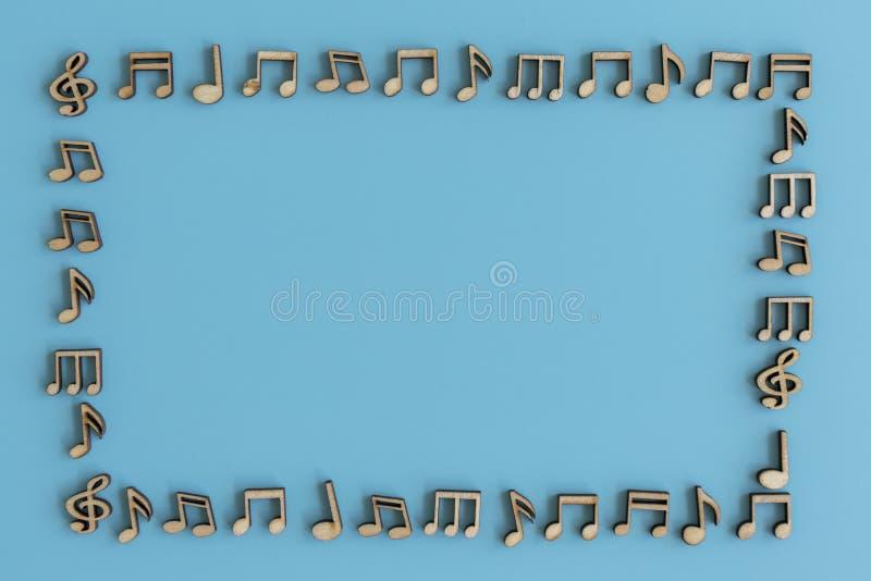 Pagina dalle note musicali su un fondo blu Note di legno su un fondo blu immagini stock