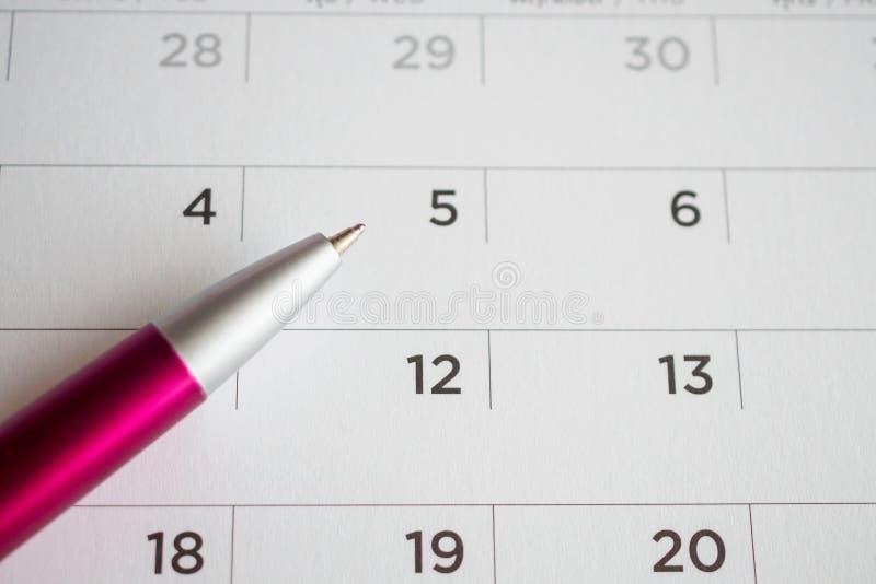 Pagina del calendario con il punto di penna alla quinta data immagini stock