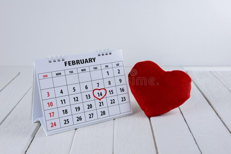 Pagina del calendario con un punto culminante del cuore scritto mano rossa il 14 febbraio del giorno di biglietti di S. Valentino immagine stock