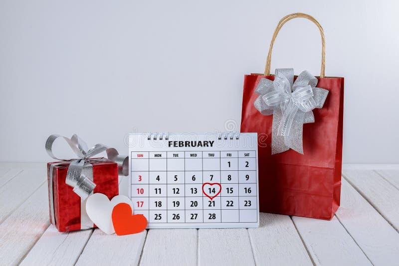 Pagina del calendario con un punto culminante del cuore scritto mano rossa il 14 febbraio del giorno di biglietti di S. Valentino immagini stock