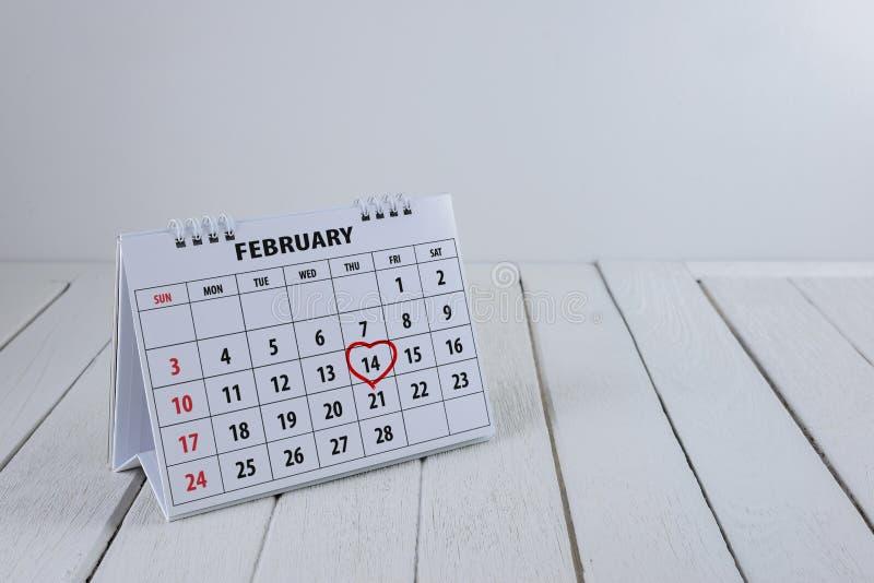 Pagina del calendario con un punto culminante del cuore scritto mano rossa il 14 febbraio del giorno di biglietti di S. Valentino fotografia stock
