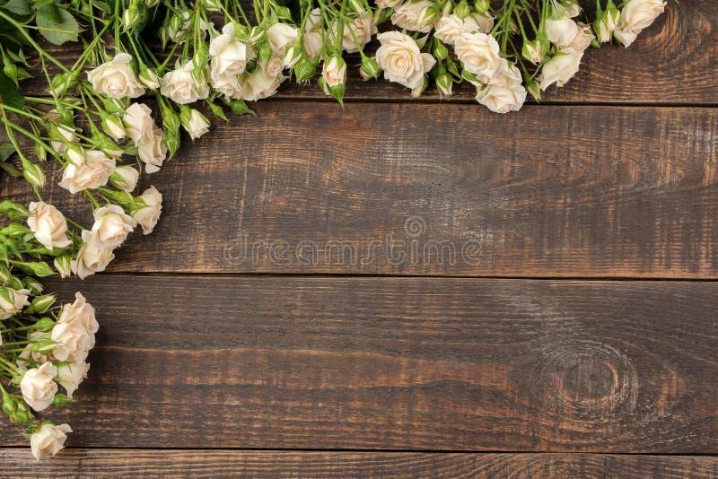 Pagina di belle mini rose su una tavola di legno marrone Bei fiori feste Vista superiore fotografia stock libera da diritti