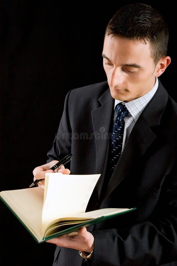 Pagina di giro dell'uomo d'affari nell'ordine del giorno immagini stock