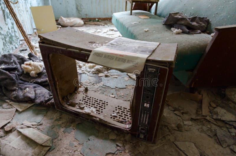 Pagina di vecchia TV sul pavimento fra rifiuti in toilette in ospedale no 126, città fantasma morta di Pripyat nella zona di alie immagini stock