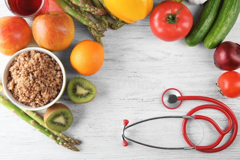 Pagina fatta con lo stetoscopio, la frutta fresca e le verdure su fondo di legno Concetto sano dell'alimento fotografie stock libere da diritti