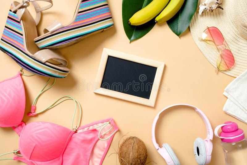 Pagina fatta degli accessori della spiaggia di estate sui precedenti gialli - swimwear, sandali, cuffie, occhiali da sole, frutti fotografia stock libera da diritti