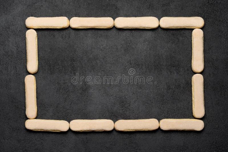 Pagina fatta dei biscotti dei ladyfingers di Savoiardi dell'italiano su backgound concreto scuro fotografia stock libera da diritti