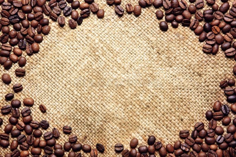 Pagina fatta dei chicchi di caffè sulla tessile del sacco fotografia stock
