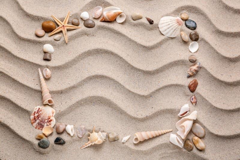 Pagina fatta delle conchiglie e delle pietre differenti sulla sabbia immagine stock