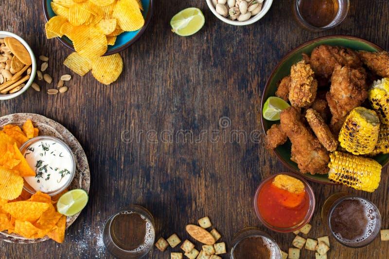 Pagina il pollo fritto, la birra, le salse, i chip, i nacho, le arachidi, pista fotografia stock libera da diritti