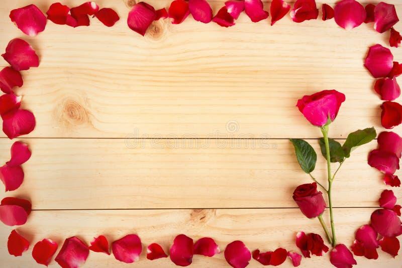 Pagina la forma fatta dai petali rosa su fondo di legno, Valentin immagine stock libera da diritti