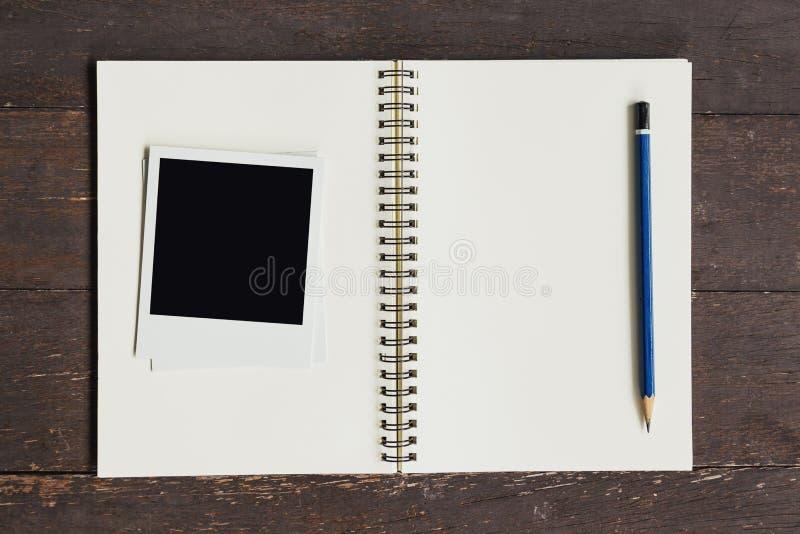 Pagina la foto ed il libro marrone sulla tavola di legno immagini stock