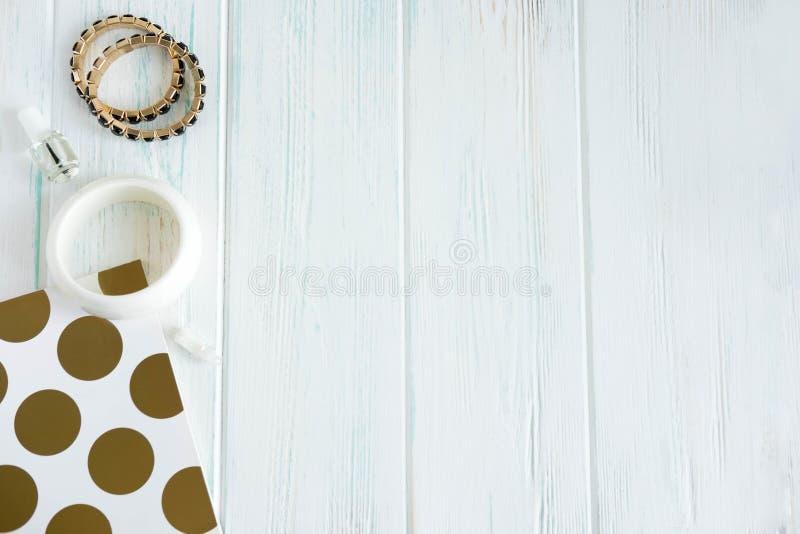 Pagina per l'insegna di bellezza con il blocco note e le decorazioni Braccialetti della mano delle donne su un fondo di legno Ins fotografie stock libere da diritti
