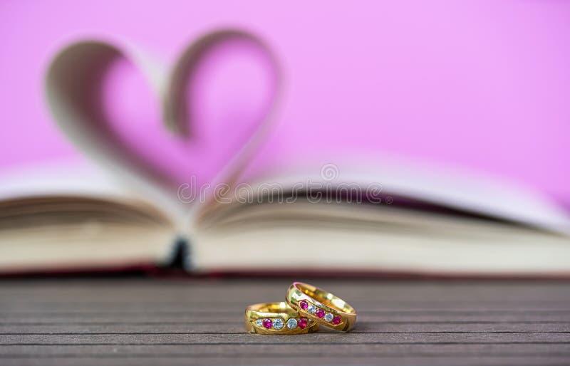 Pagina's van boek gebogen hart vorm en het wieden van ring stock afbeelding
