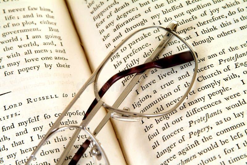 Paginaciones del libro del siglo XVIII con las gafas imagen de archivo