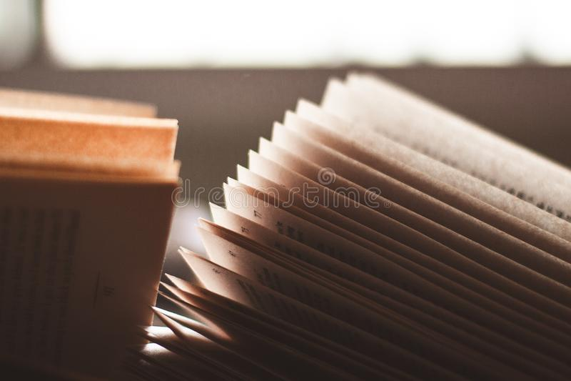 Pagine aperte di un libro indietro acceso dalla luce della finestra fotografie stock