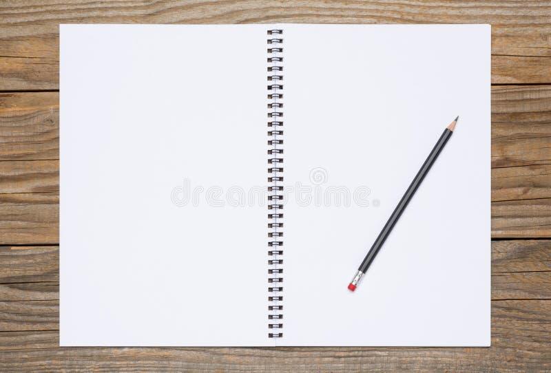 Pagine in bianco di uno sketchbook aperto con una matita nera fotografia stock