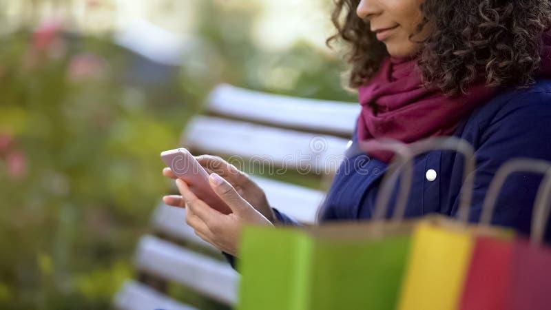 Pagine di sorveglianza della donna sullo smartphone, scegliente gli oggetti online, acquisto mobile immagine stock libera da diritti