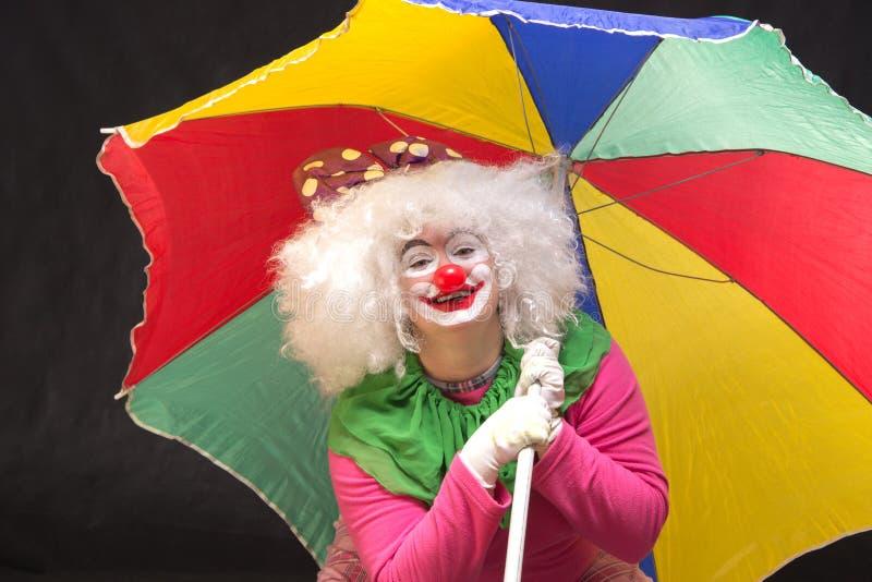 Pagliaccio divertente allegro con di un ombrello colorato multi su un backg nero fotografie stock libere da diritti