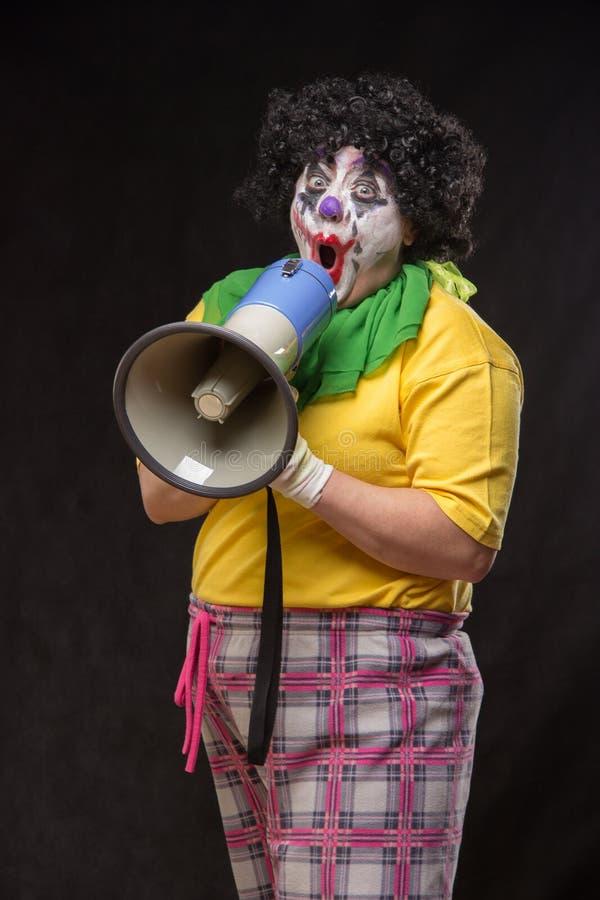 Pagliaccio spaventoso che grida in un megafono su un fondo nero fotografia stock libera da diritti