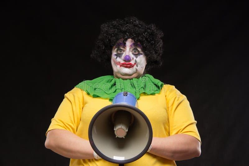 Pagliaccio spaventoso che grida in un megafono su un fondo nero fotografia stock