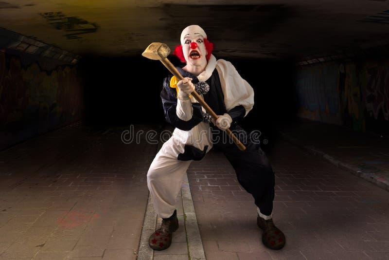 Pagliaccio spaventoso con un martello fotografia stock libera da diritti